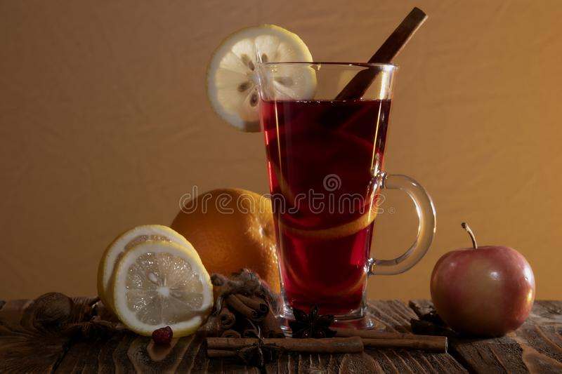 A glass of mulled wine with an orange peel and a slice of lemon, cinnamon sticks, star anise and chopped citrus and apple on a royalty free stock photos