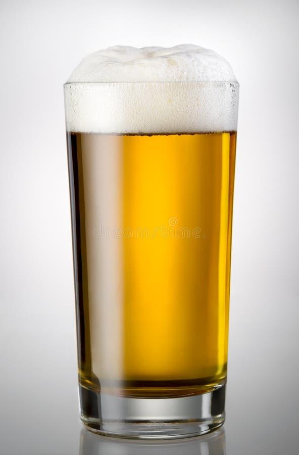 Glass mycket av öl och skum arkivfoto