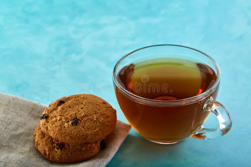 Glass närbild för kopp te- och havremjölchokladkakor på blå bakgrund royaltyfria foton