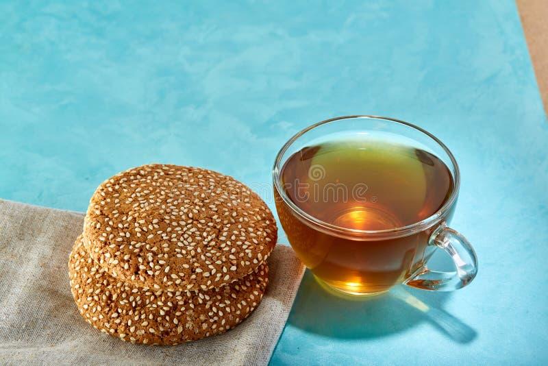 Glass närbild för kopp te- och havremjölchokladkakor på blå bakgrund royaltyfri foto