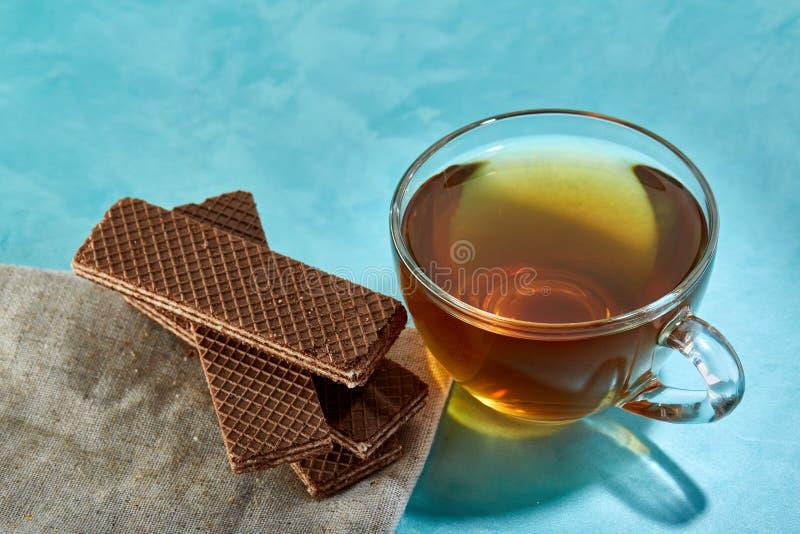 Glass närbild för kopp te- och havremjölchokladkakor på blå bakgrund arkivfoton