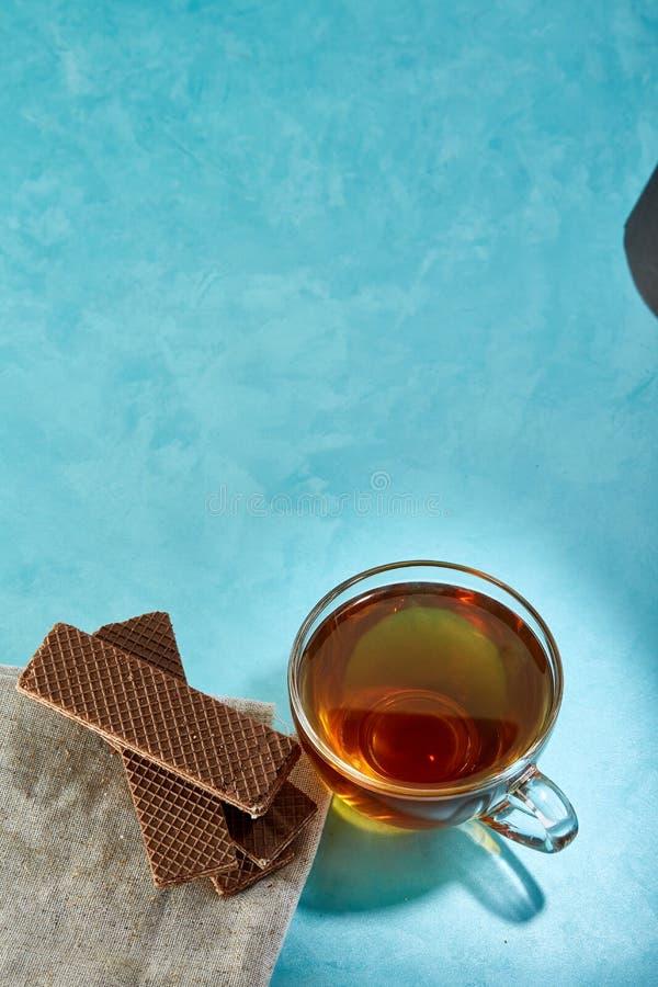 Glass närbild för kopp te- och havremjölchokladkakor på blå bakgrund royaltyfri fotografi