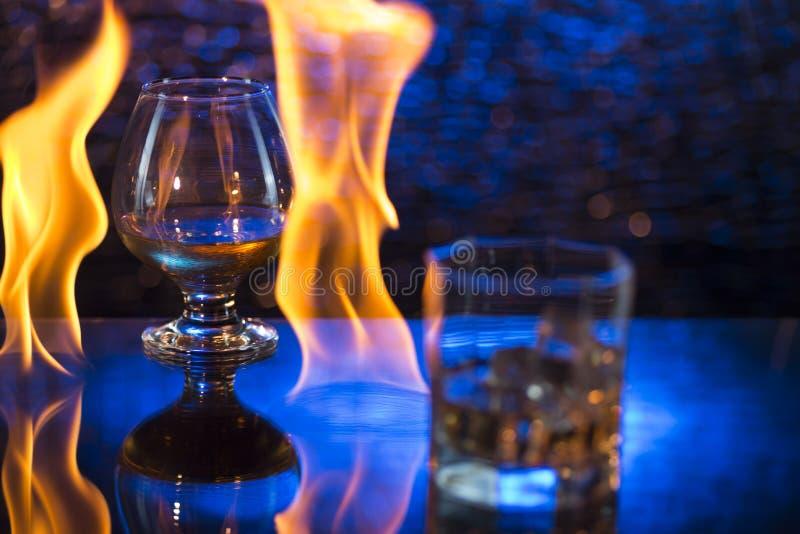 Glass nolla-whisky med is och vinglaset av konjak och brand flammar på bokehbakgrund arkivbilder