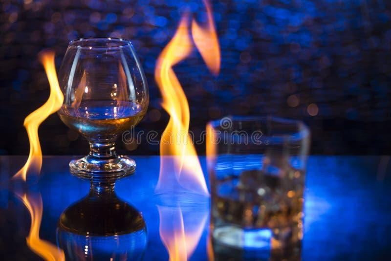 Glass nolla-whisky med is och vinglaset av konjak och brand flammar på bokehbakgrund fotografering för bildbyråer
