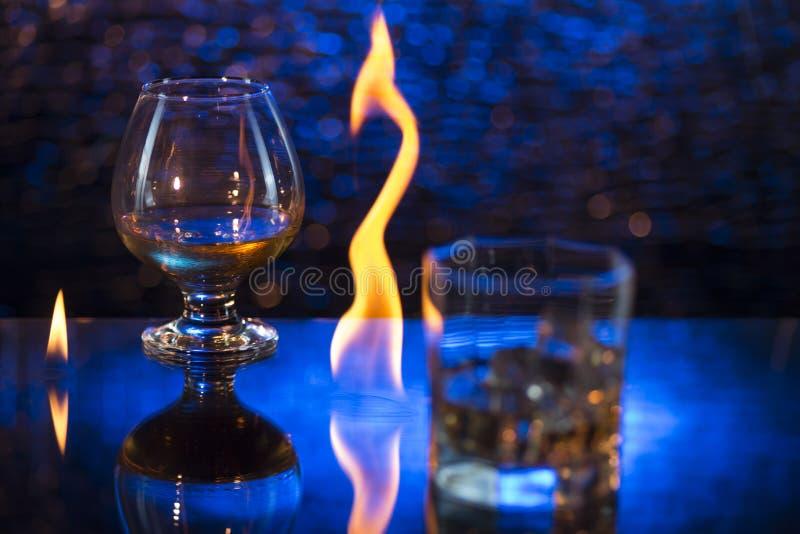 Glass nolla-whisky med is och vinglaset av konjak och brand flammar på bokehbakgrund arkivbild