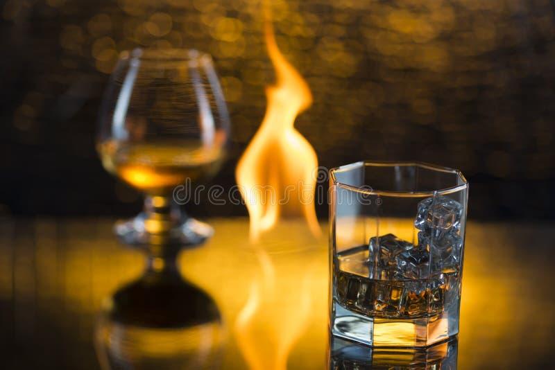 Glass nolla-whisky med is och vinglaset av konjak och brand flammar på gul bokehbakgrund royaltyfri fotografi
