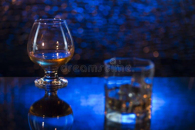 Glass nolla-whisky med is och vinglaset av konjak på blå bokehbakgrund royaltyfri bild