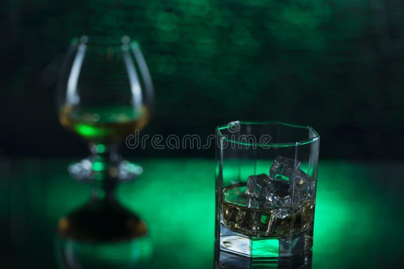 Glass nolla-whisky med is och vinglaset av konjak på grön bokehbakgrund arkivbilder
