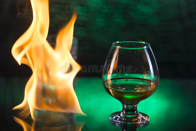 Glass o whisky with ice and wineglass of cognac and fire flames on green bokeh background stock photo