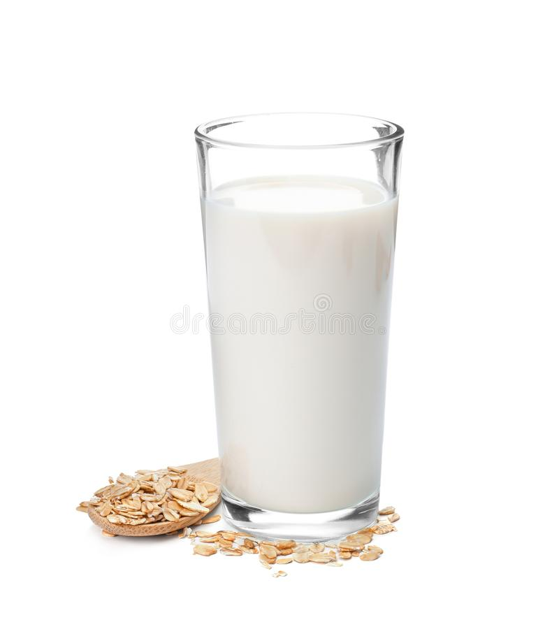 Glass with oat milk and flakes. On white background royalty free stock image