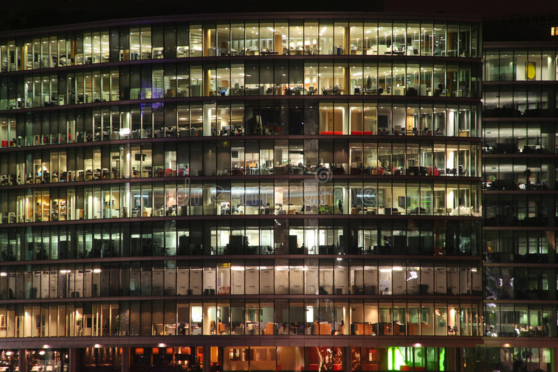 Glass Office Tower. Office tower with lighted windows in late evening, people working late royalty free stock photos