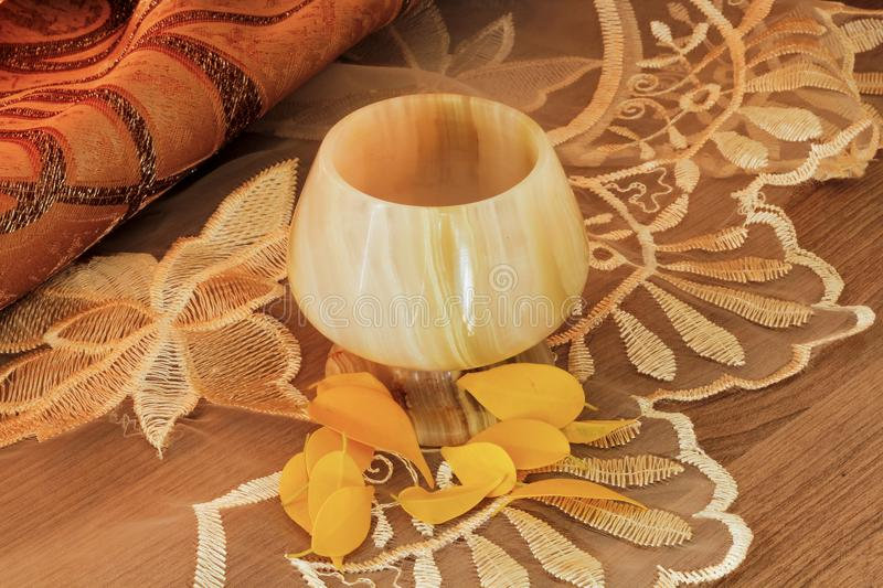A glass of onyx. And yellow autumn leaves stock photo