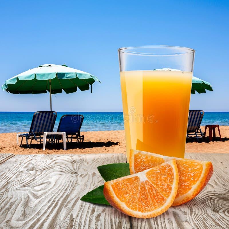 Glass of orange juice against beach royalty free stock image