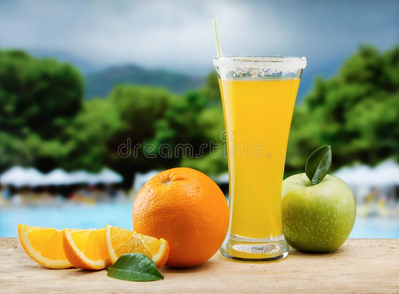 Glass of orange juice on a beach. Table stock images