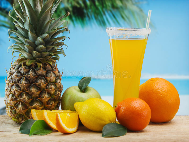 Glass of orange juice on a beach. Table royalty free stock photos