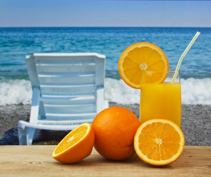 Glass of orange juice on a beach. Table stock photography