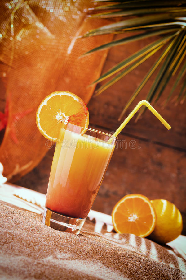 Glass of orange juice on a beach table. With palm tree royalty free stock photography