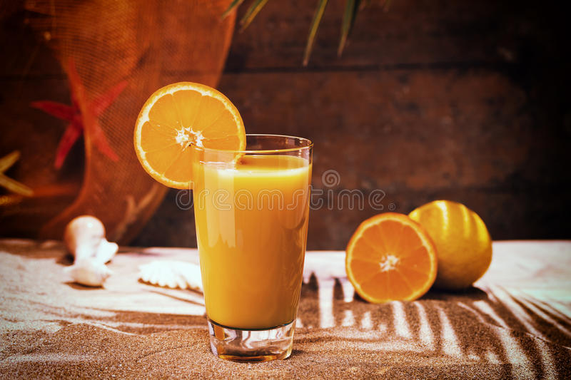 Glass of orange juice on a beach table. With palm tree royalty free stock photos
