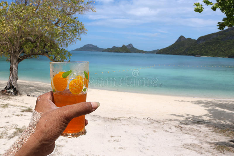 Glass of orange juice on the beach. Glass of orange juice on the beach with views of the archipelago Islands,Thailand royalty free stock image