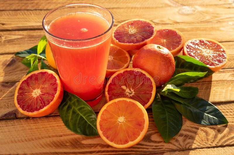 Glass With Orange Juice Of Blood Oranges With Fresh Fruits. Outdoor Shot In The Sunshine stock photos