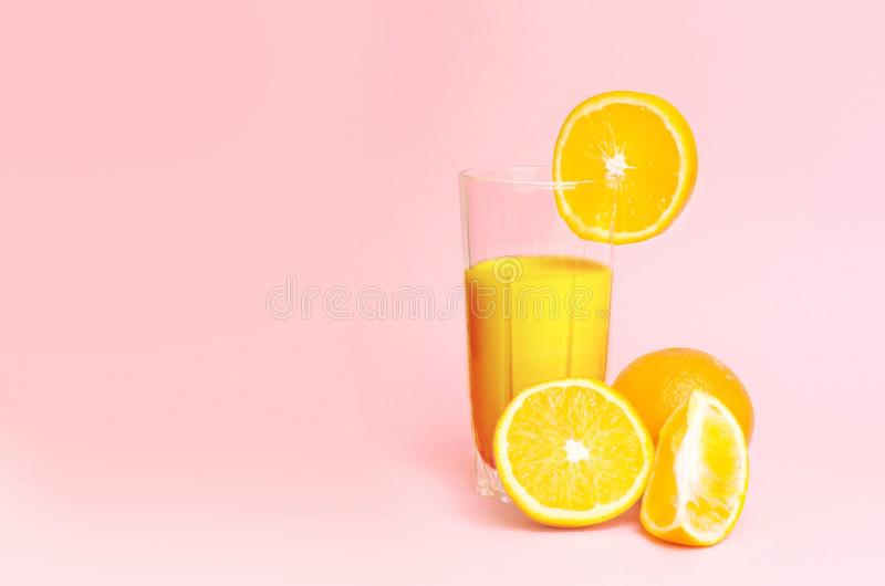 A glass with orange juice with the cut oranges on a pink background. Juicy color scale, pin up, pop up styles. Food for breakfast stock photos