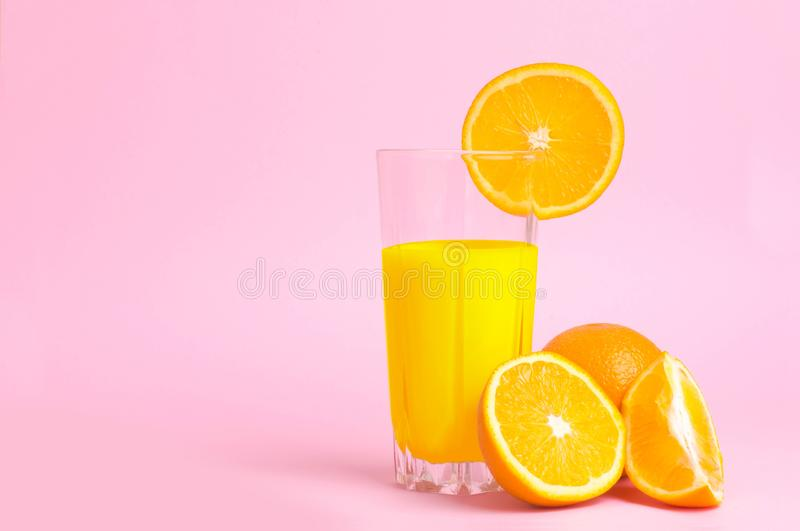 A glass with orange juice with the cut oranges on a pink background. Juicy color scale, pin up, pop up styles. Food for breakfast royalty free stock photo