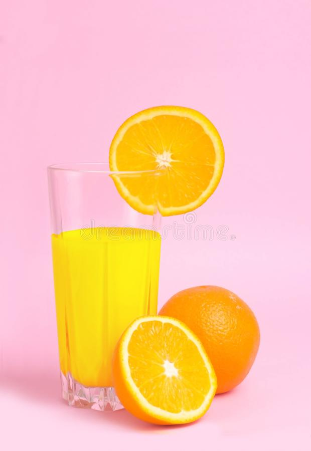 A glass with orange juice with the cut oranges on a pink background. Juicy color scale, pin up, pop up styles. Food for breakfast stock photography