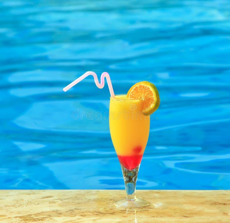 Glass of orange juice is on edge of pool stock photo