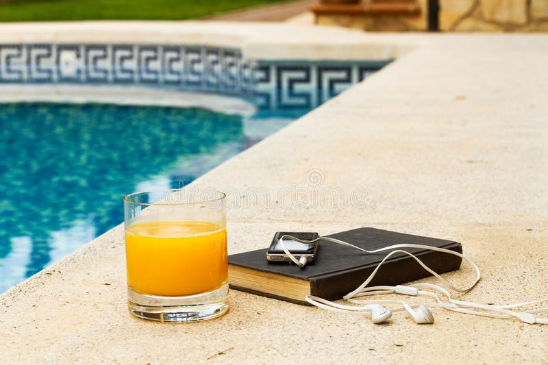 A glass of orange juice on the edge of the pool. In summer royalty free stock photos
