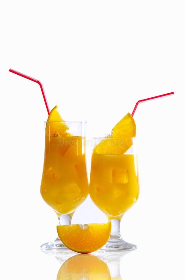 A glass with orange juice, fruit slices, ice, sliced orange on a white table. White background royalty free stock photos