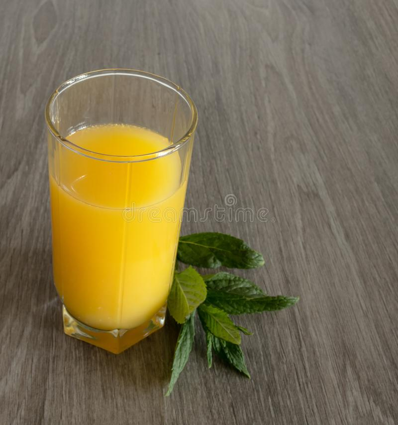 A glass of orange juice next to which is a sprig of mint on a wooden surface stock photo