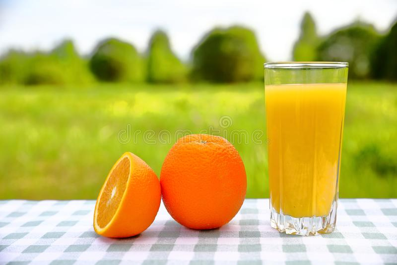 A glass of orange juice with oranges on a green-and-white checkered tablecloth, blurred green natural background. On a sunny day stock photos