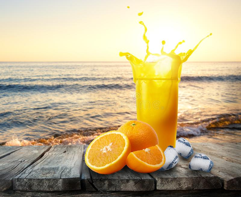 Glass of orange juice with splash of oranges and ice on wooden t. Able. A glass of juice stands on a table amid the sea sunset. The concept of rest and vacations stock images