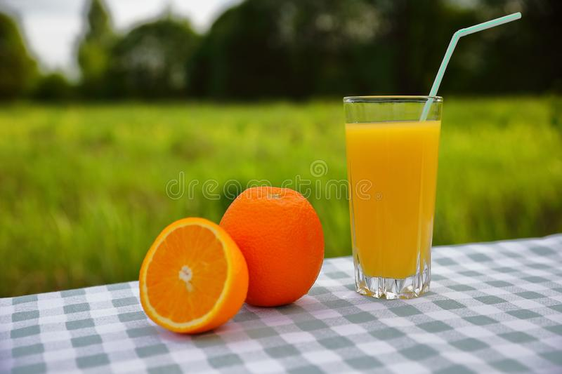 A glass of orange juice with a straw, oranges on a green-and-white checkered tablecloth, blurred green natural background. On a sunny day stock images
