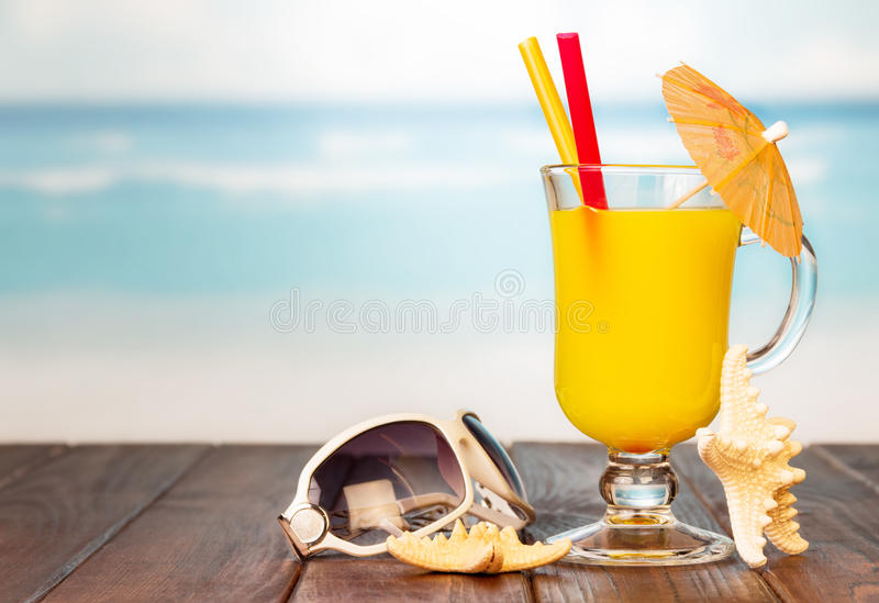 Glass of orange juice and sunglasses on beach. stock images