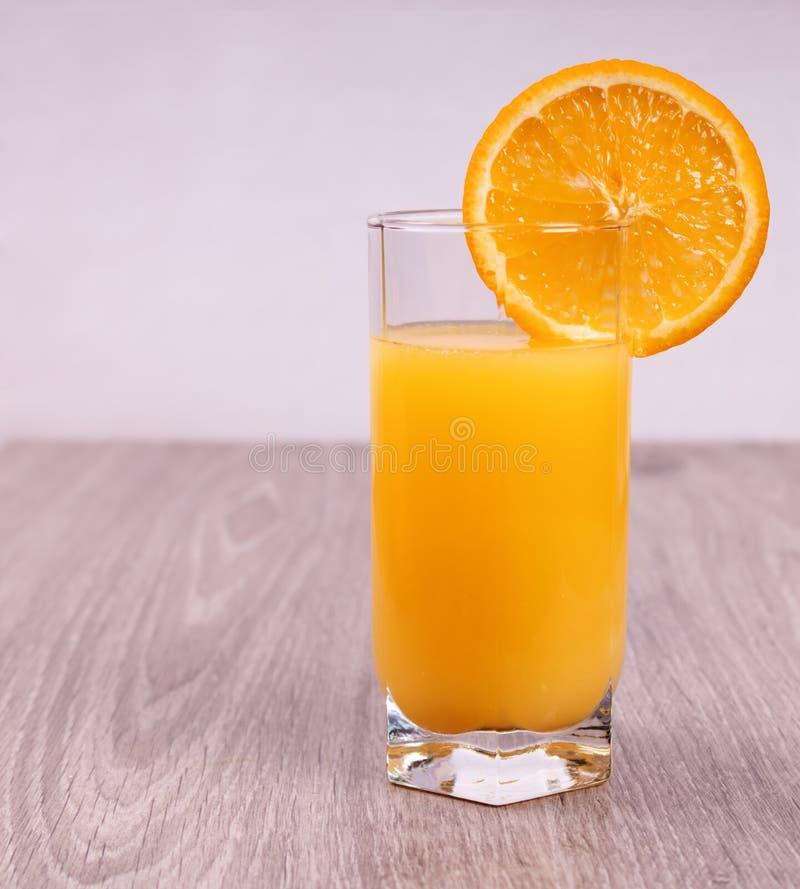 Glass with orange slice on light wooden background stock photo