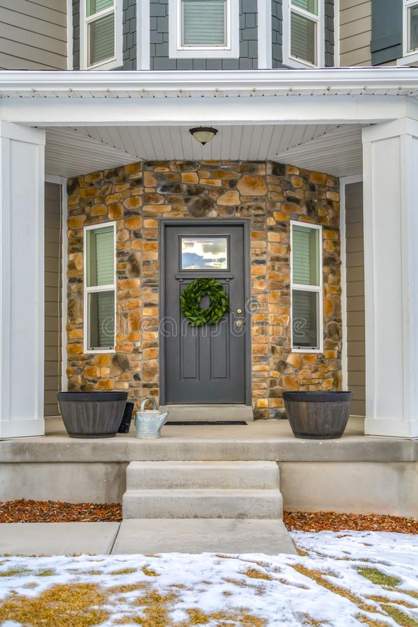 Glass paned front door and windows on the half hexagon shaped wall of a home. Snowy yard and stairs leads to the porch with pots and pillars royalty free stock photography