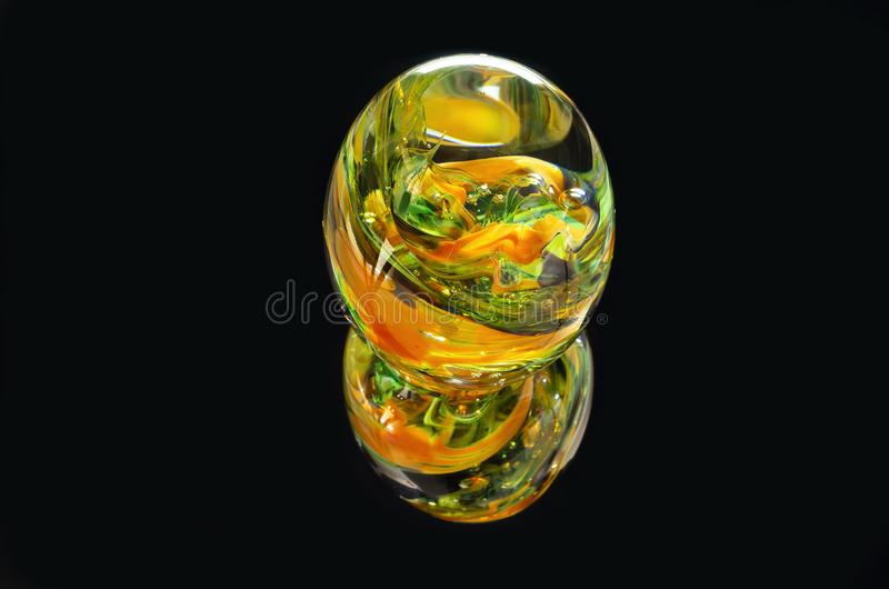 Glass Paperweight Closeup Against Black. Multicolored glass paperweight and reflection isolated against black stock photography