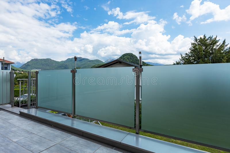 A glass parapet of a modern building balcony overlooking hills stock image