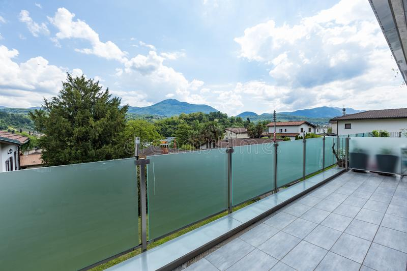 A glass parapet of a modern building balcony overlooking hills stock images