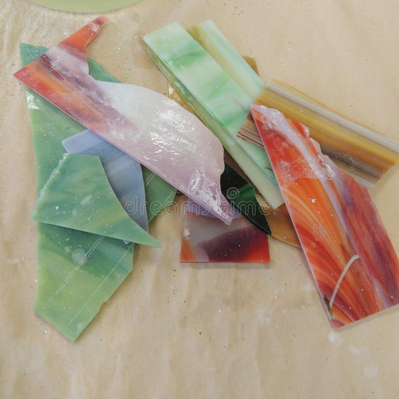 Glass parts for stained glass project. Glass pieces on table used to create stained glass artwork stock image