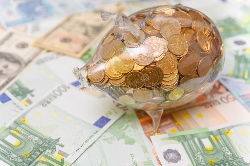 Glass piggy bank full of golden coins over a background made of Euro and Dollar bank notes bills. royalty free stock photography