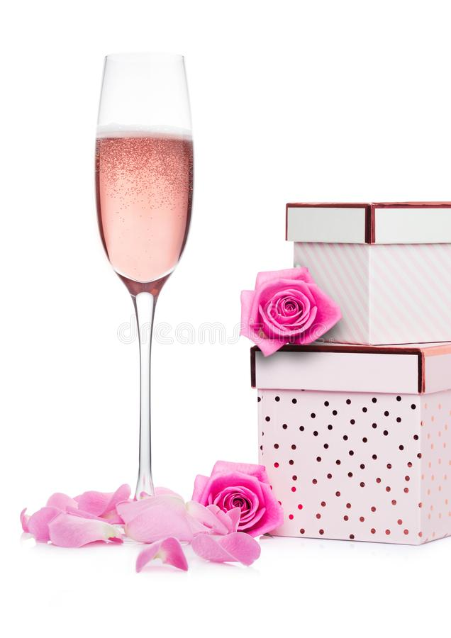 Glass of pink champagne with pink gift box royalty free stock photos