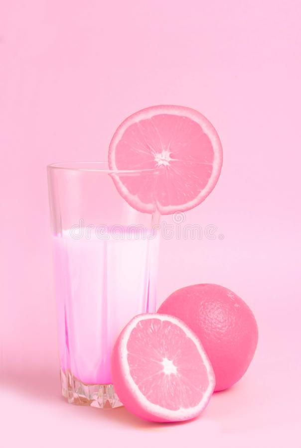 A glass with pink orange juice with the cut oranges on a pink background. Juicy color scale, pin up, pop up styles. Food for break stock photography