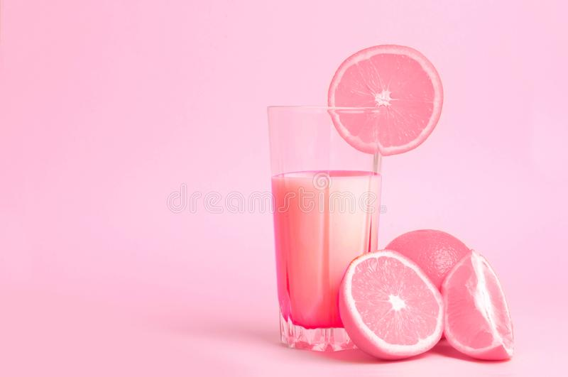 A glass with pink orange juice with the cut oranges on a pink background. Juicy color scale, pin up, pop up styles. Food for break. Fast, a healthy drink with stock photo