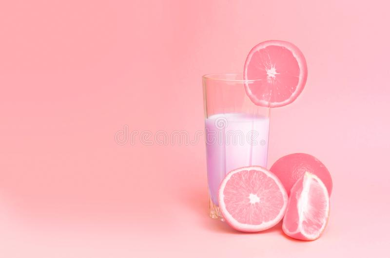 A glass with pink orange juice with the cut oranges on a pink background. Juicy color scale, pin up, pop up styles. stock images