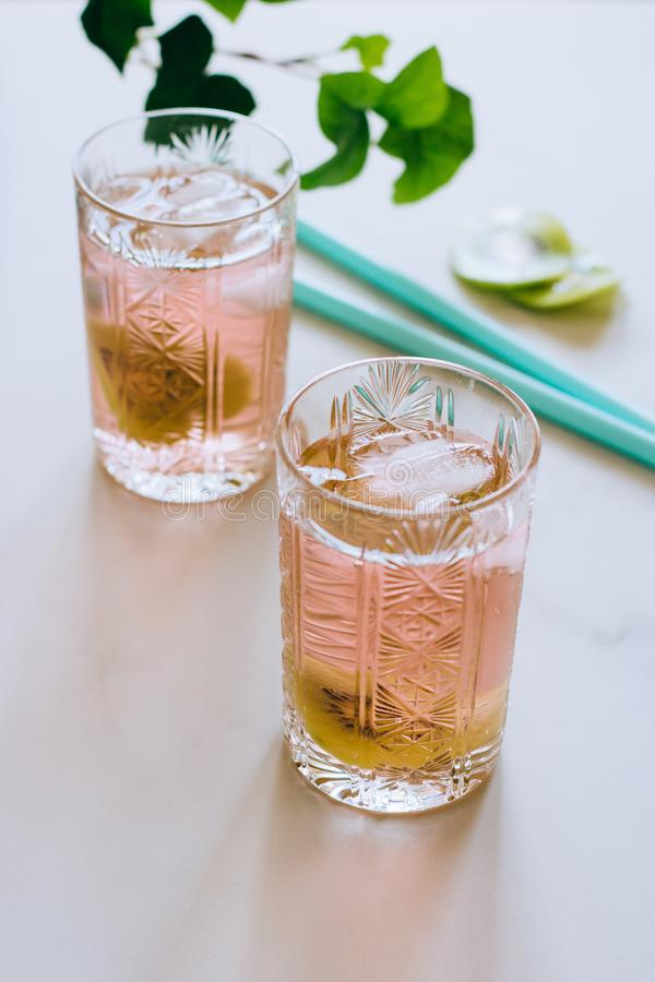 A glass of pink wine in a crystal glass on a marble background, green ivy. And bright sun stock photography