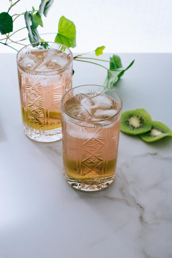 A glass of pink wine in a crystal glass on a marble background, green ivy. And bright sun royalty free stock image