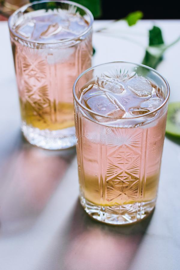 A glass of pink wine in a crystal glass on a marble background, green ivy. And bright sun stock photo