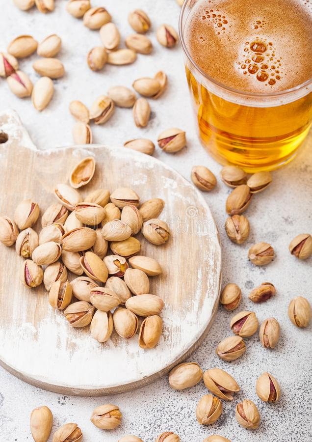 Glass pint of craft lager beer with pistachio nuts on stone kitchen table background. Beer and snack royalty free stock images